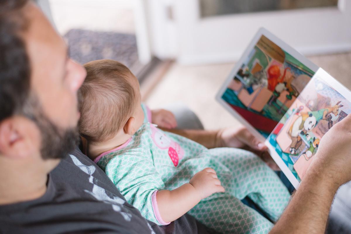 Mann schaut sich mit Kleinkind ein Bilderbuch an