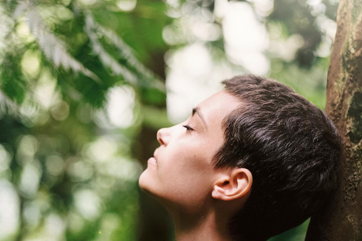 Mensch mit geschlossenen Augen im Wald