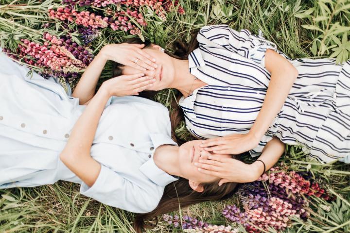 Zwei Frauen, die sich gegenseitig die Augen zuhalten