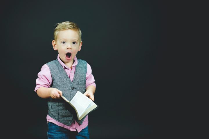 Kind blickt von einem geöffneten Buch mit offenem Mund auf