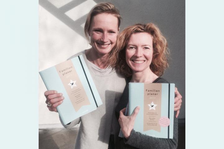 Autorin und Lektorin halten ein Buch hoch