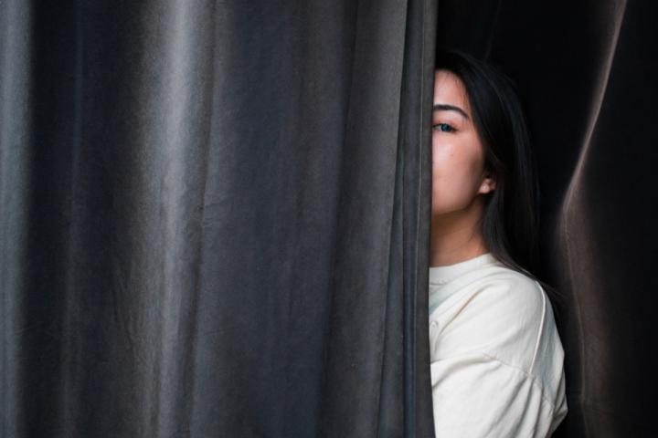 Frau versteckt sich hinter einem Vorhang